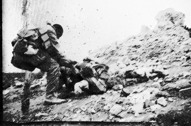 Gunner trascina lontano dalla battaglia un compagno ferito gravemente. Sta superando un ostacolo e tira su Disperazione.