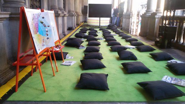 Una serie di cuscini a terra e un televisore in fondo.